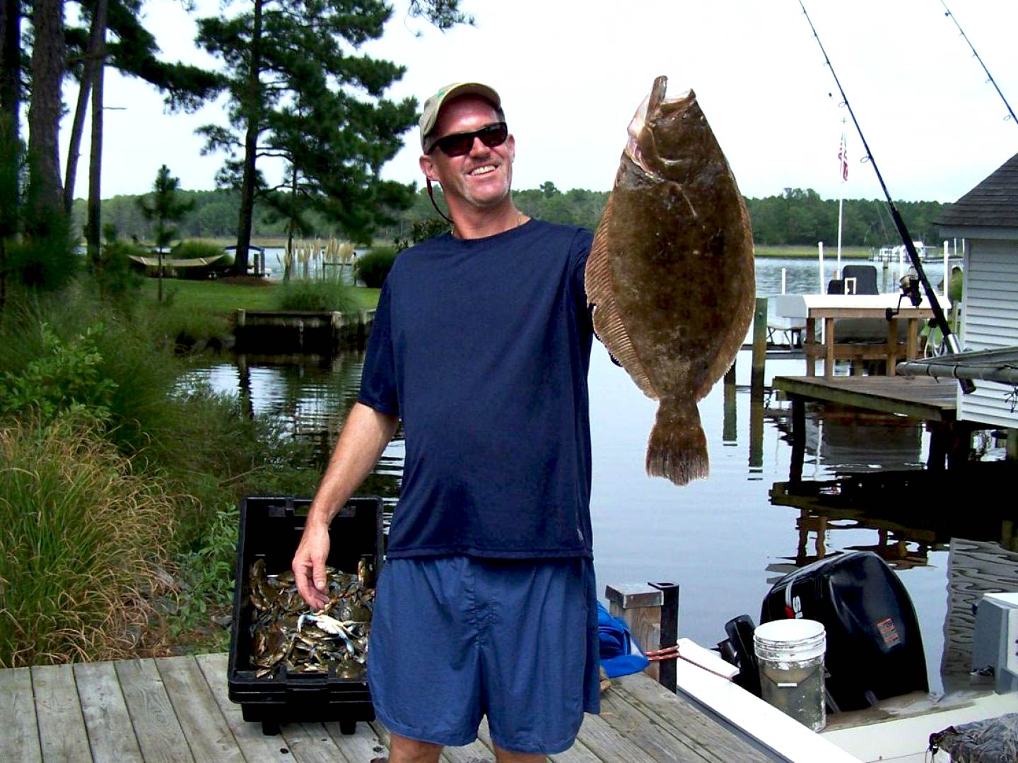 A man holding a Flounder after a day of fishing