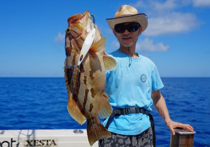 An angler in a blue shirt and a white hat holding a grouper fish with a white slow pitch jig hanging out of its mouth.