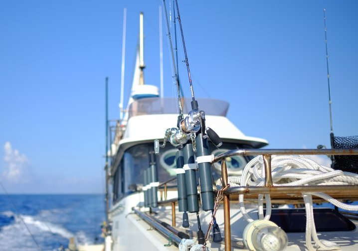 The side of a boat looking towards the stern with three slow pitch jigging rods in rod holders attached to a bronze rail in the foreground