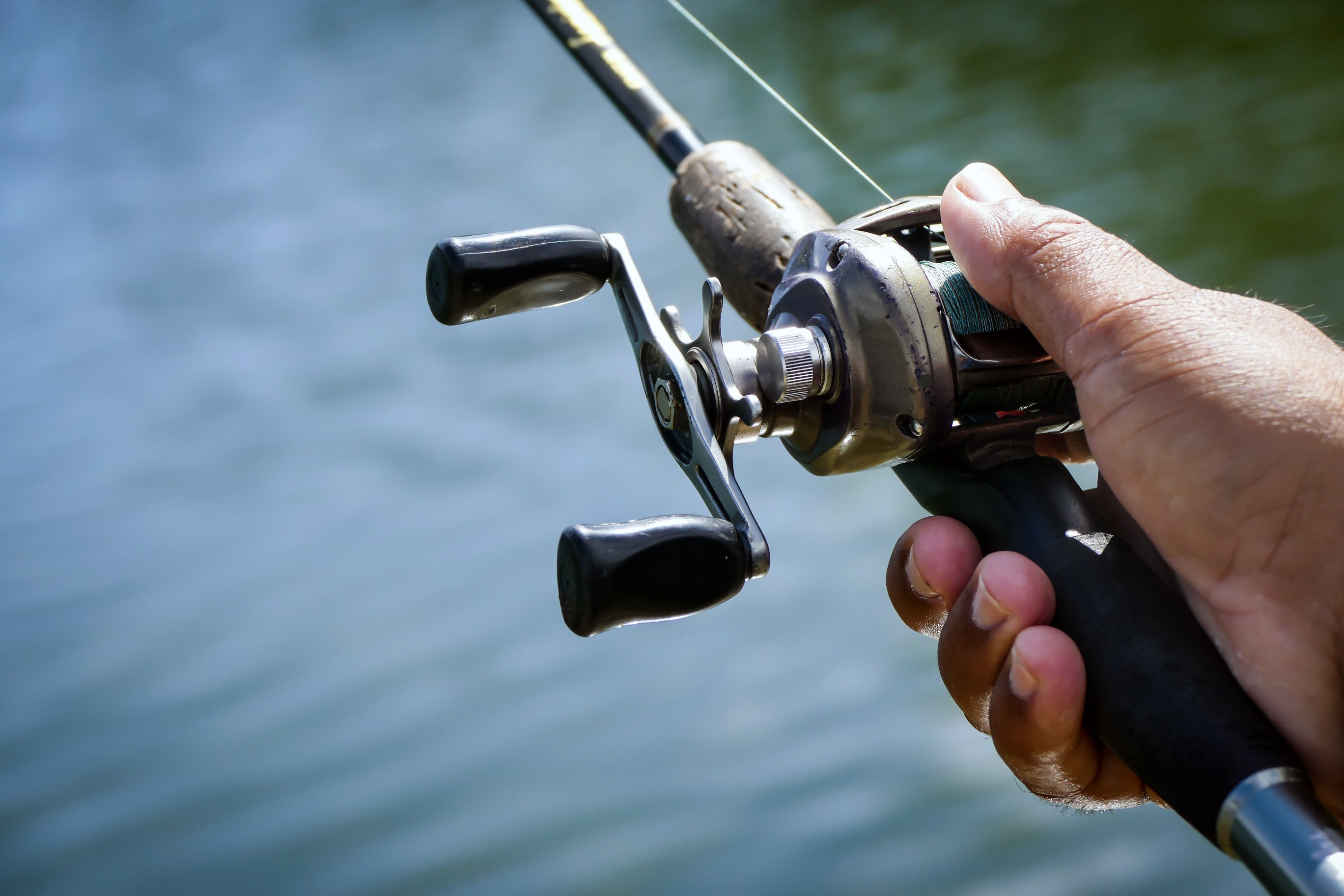types of fishing reels: a baitcasting reel in the hand of an angler
