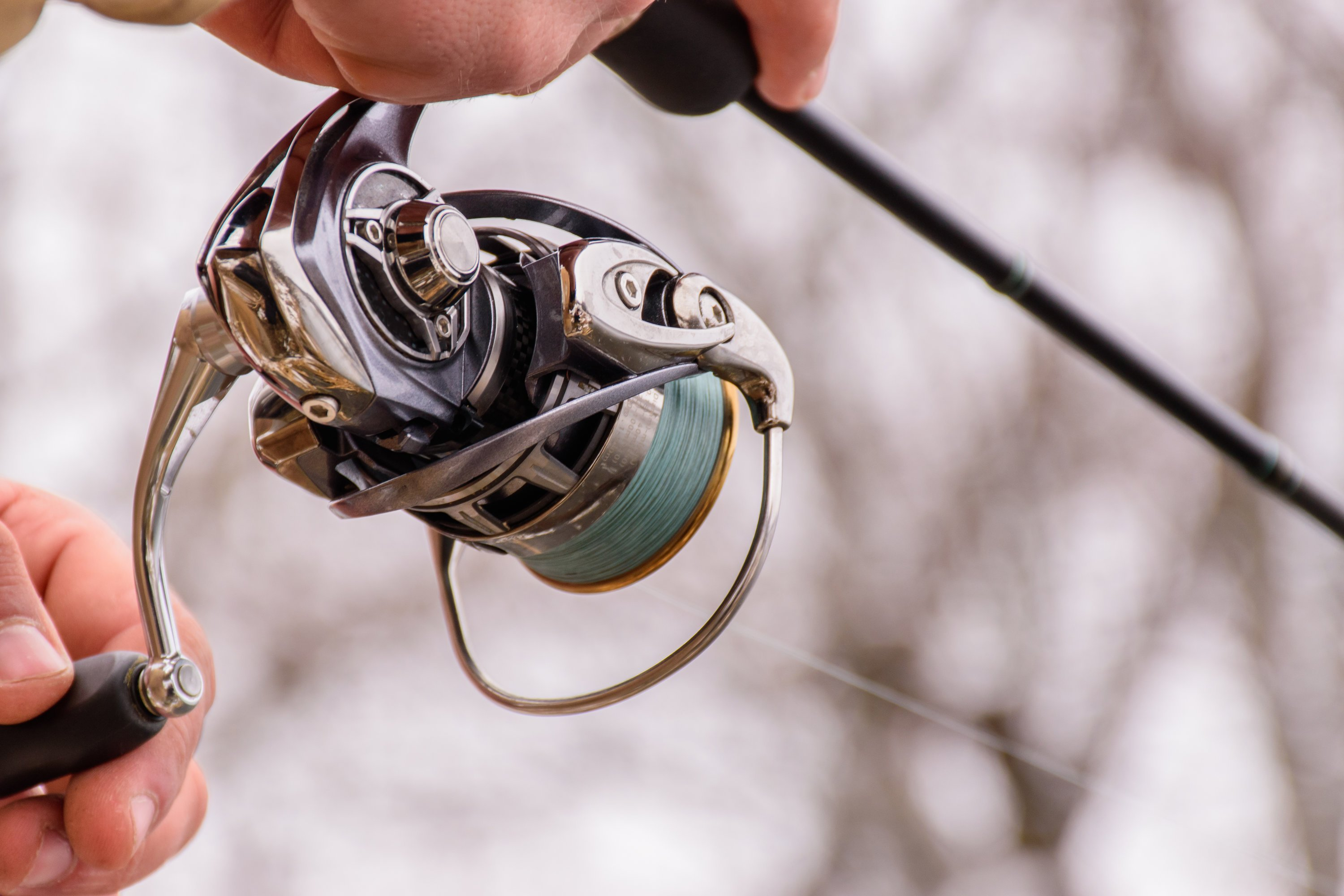 a closeup of a spinning reel on a fishing rod