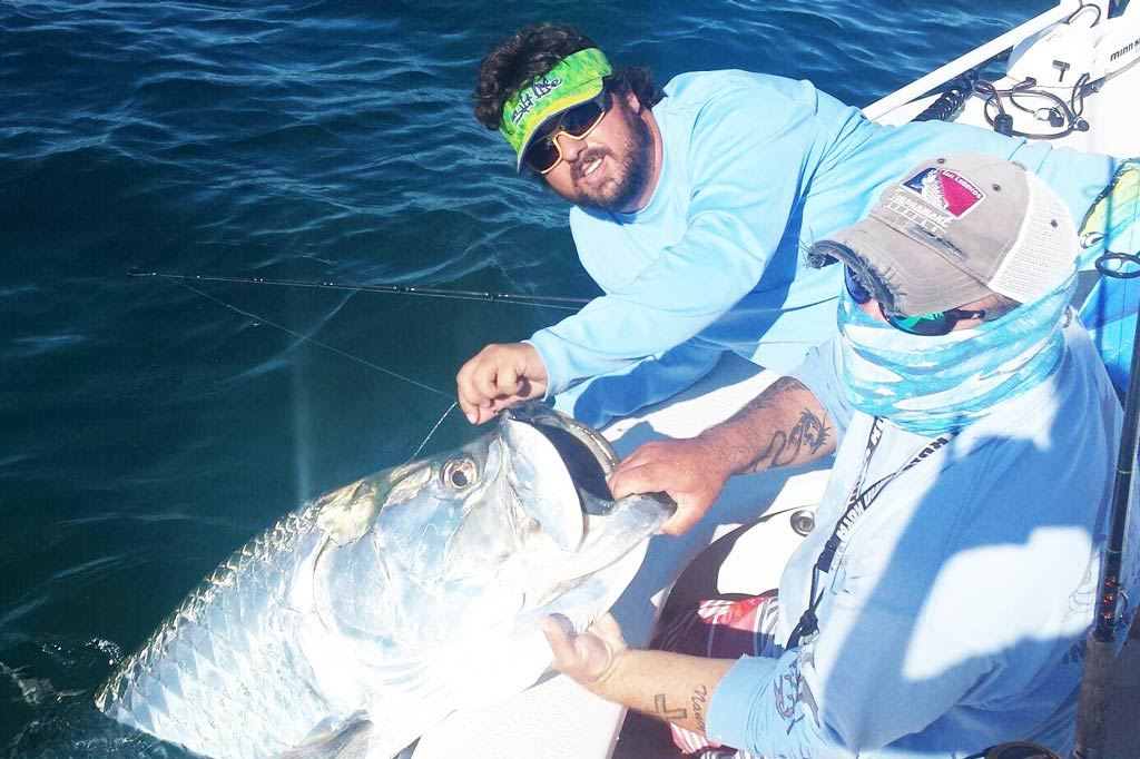Two anglers on the edge of a boat holding a Tarpon by the mouth