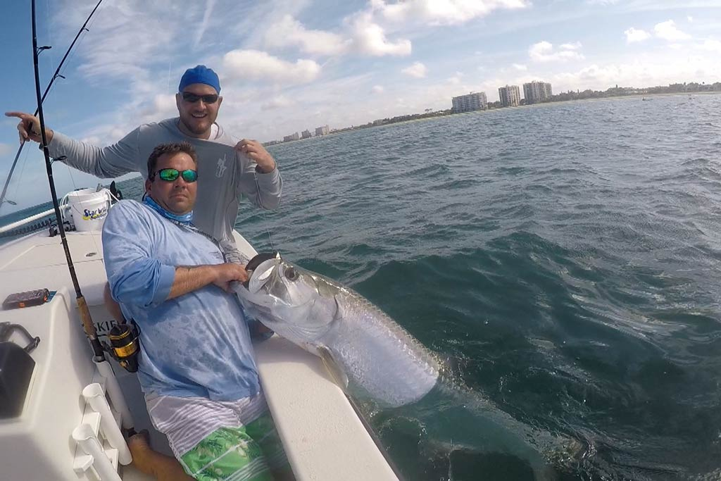 Two fishermen standing on a boat, holding onto a big Tarpon still in the water, with Florida shore in the background