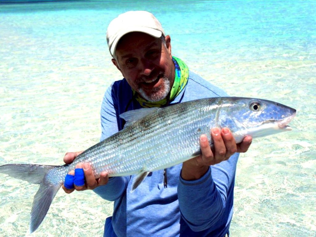 A man holding a Bonefish in the shallow water on the beach