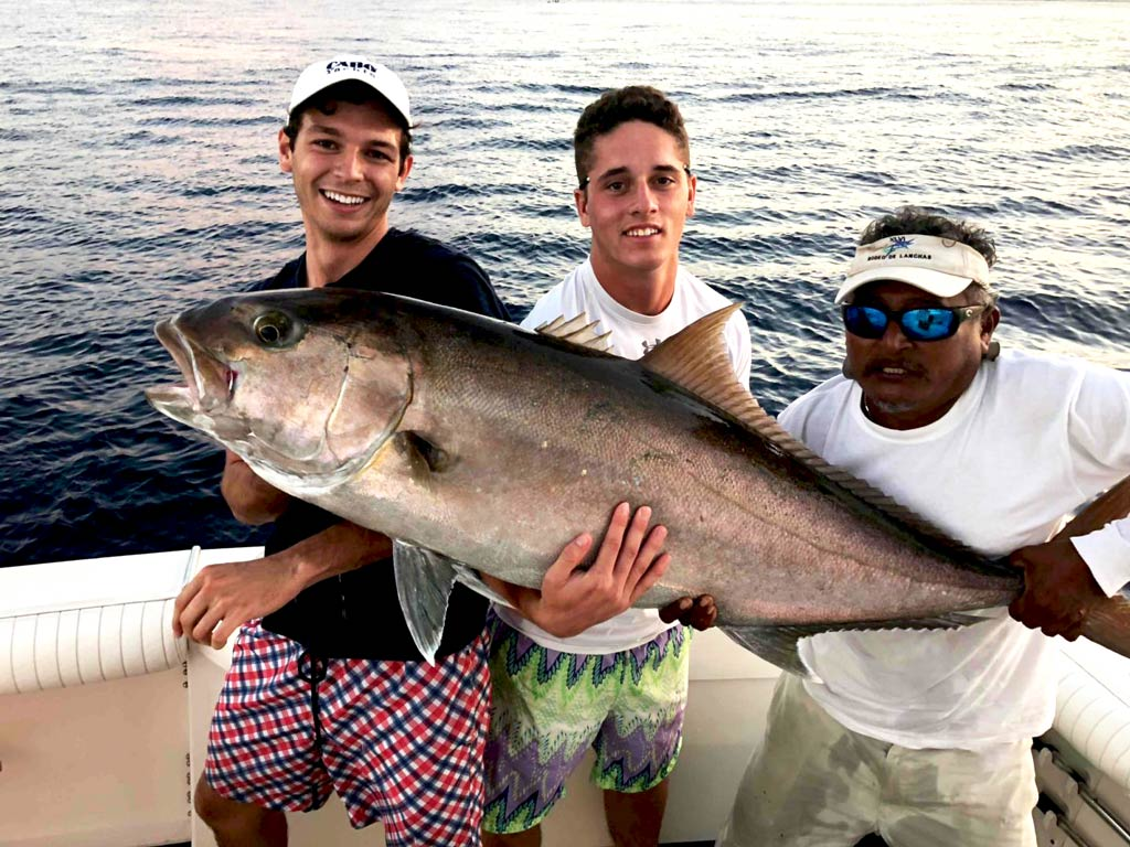 Three anglers holding a big Amberjack on a boat in the waters of Cozumel