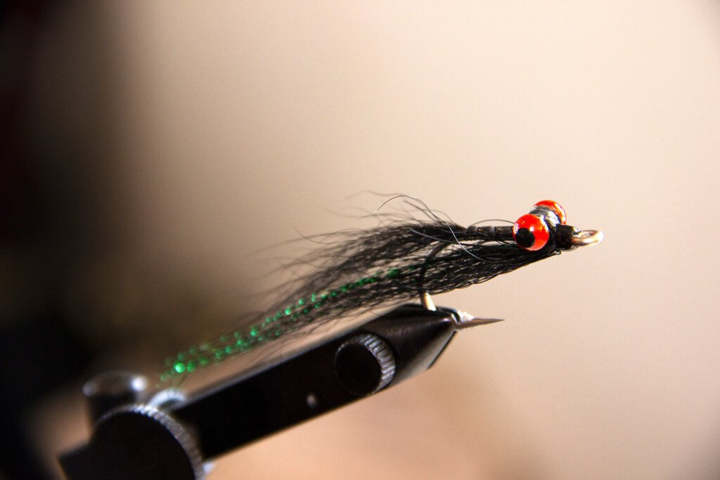 A Clouser Minnow on a fly tying vise
