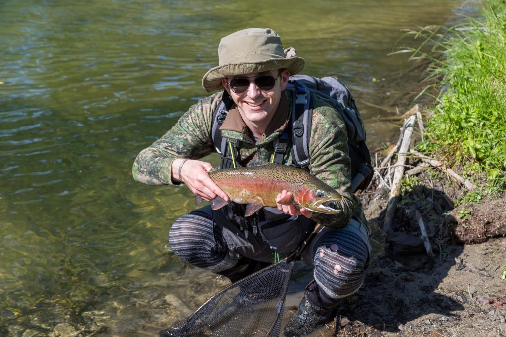 Man holding rainbow trout on river in New Zealand