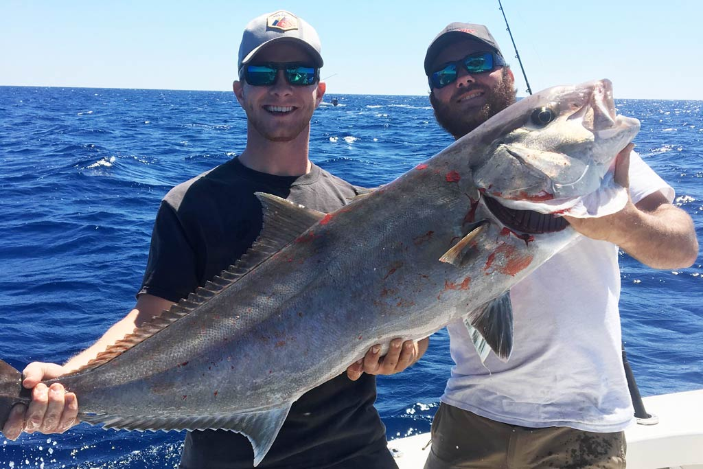 Two smiling anglers in caps and sunglasses holding a big Amberjack while standing on a boat