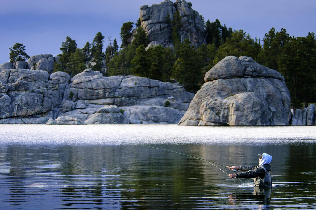 A man fly fishing in a lake in South Dakota's Black Hills, on of the top spring fishing spots in the US