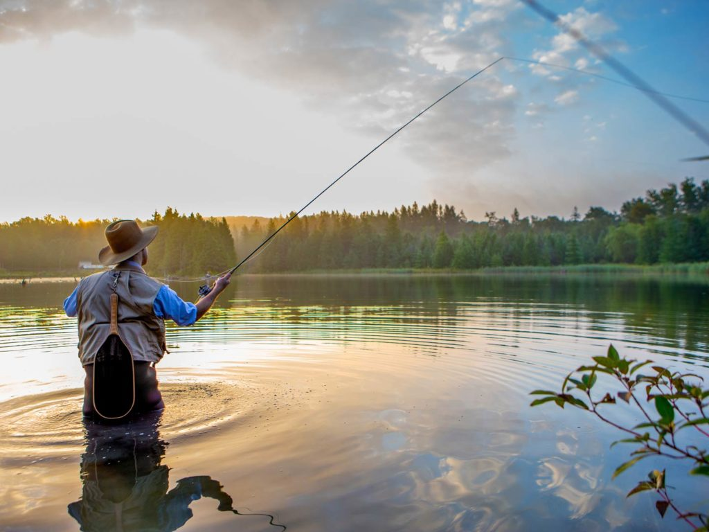 A young man fly fishing at sunrise