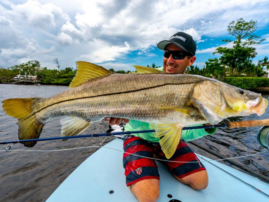 An angler holding a big Snook on a boat in the inshore waters