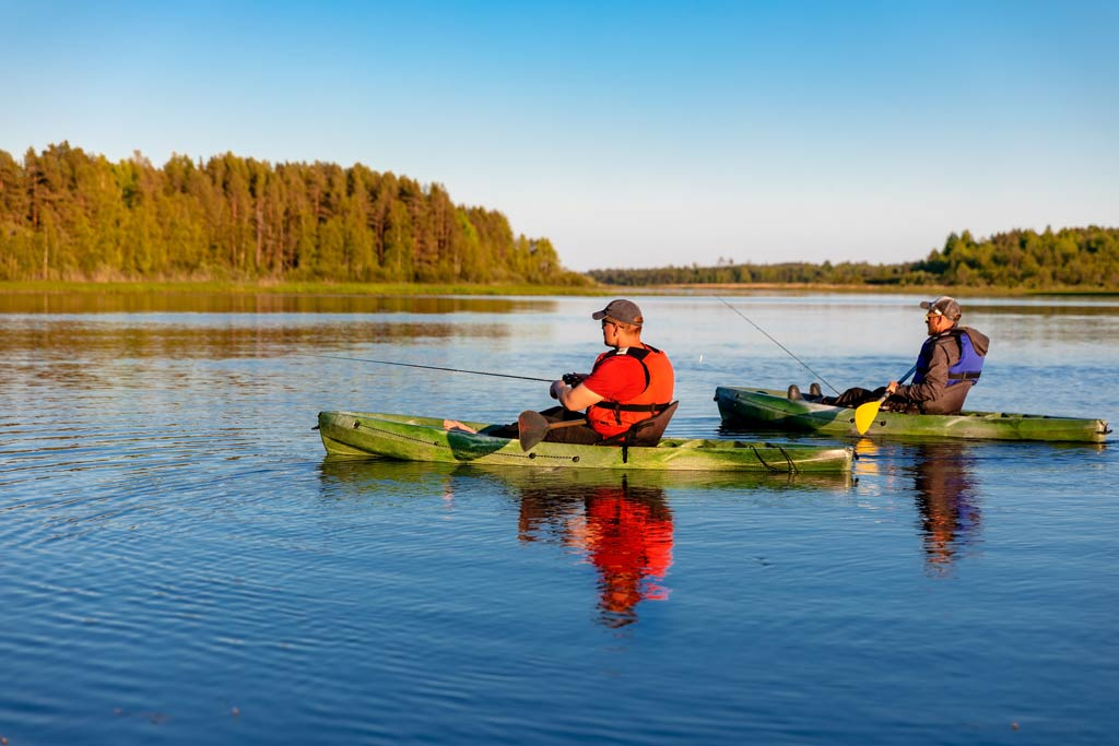 Two anglers kayak fishing in sunny weather on a lake.