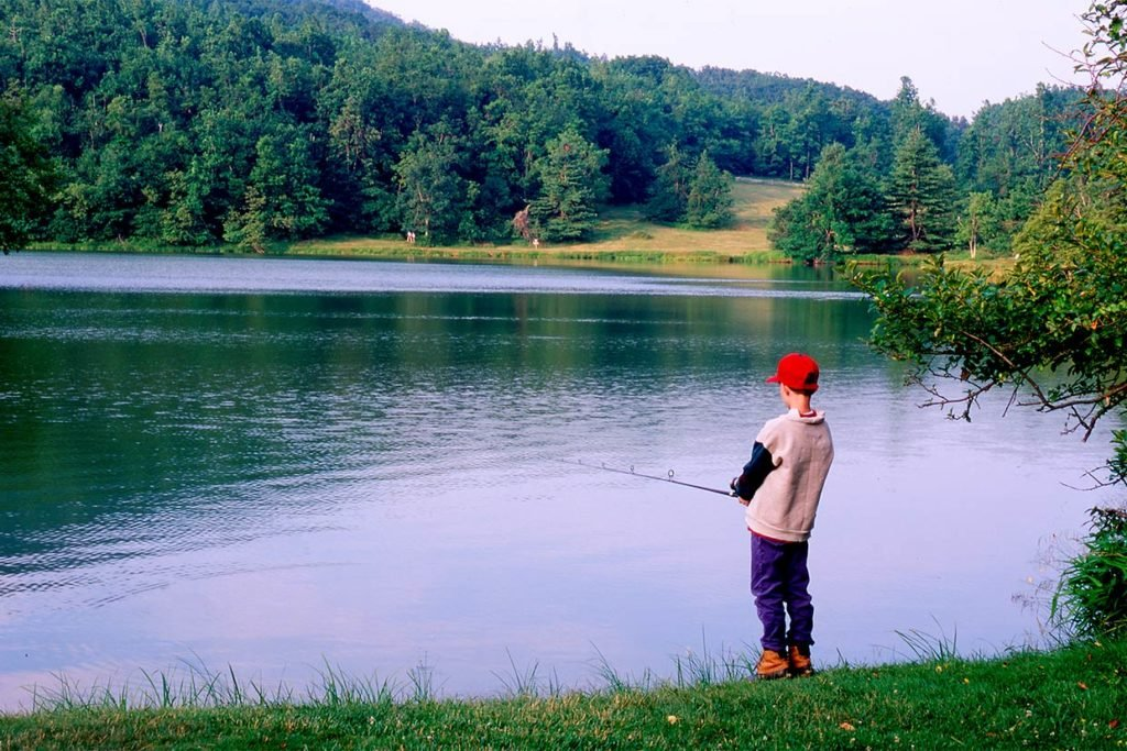 A young angler stands alone near a lake in Virginia