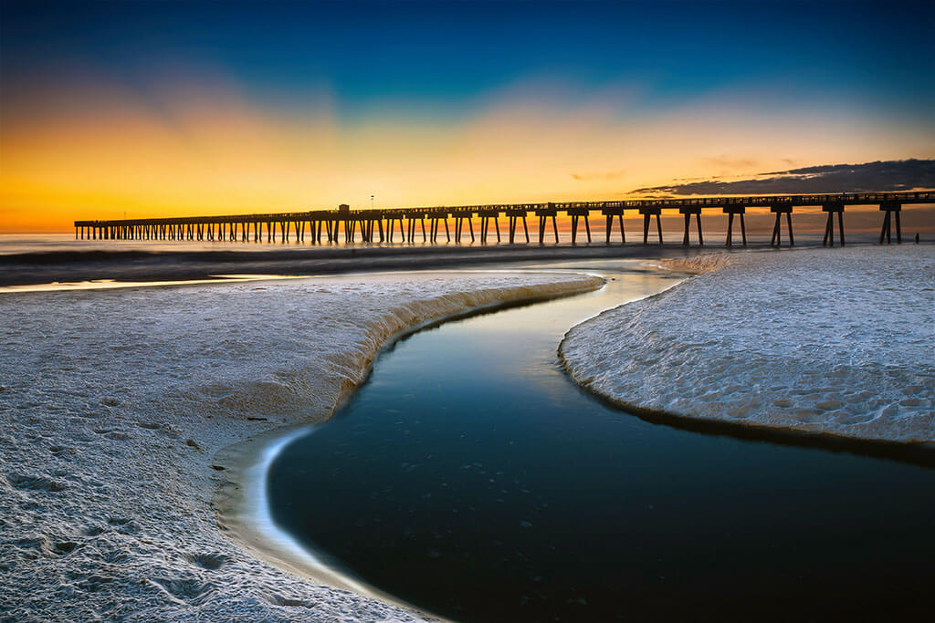 A view of Panama City Beach fishing pier at sunset, with white sand and a shallow tidal channel in the foreground