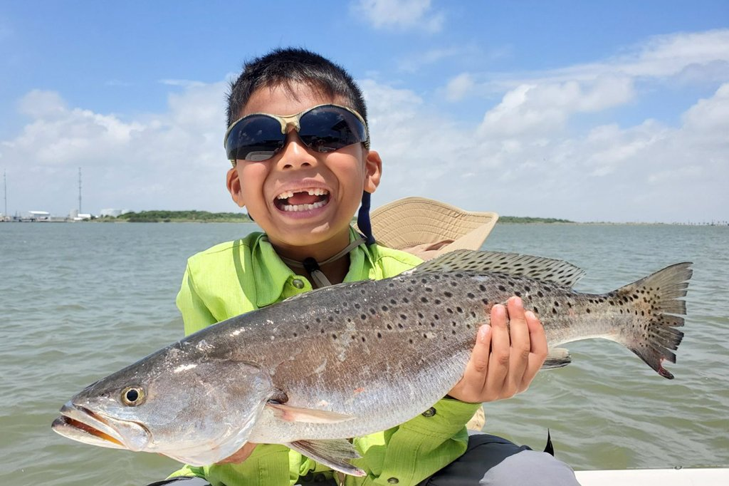 A young child holds a Speckled Trout up to the camera on a sunny day with the water behind him