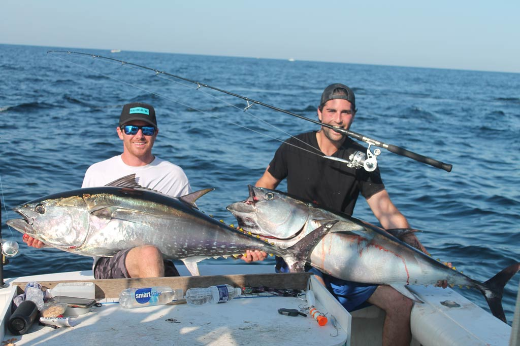 Two anglers holding a Yellowfin Tuna each aboard a Montauk fishing chater.