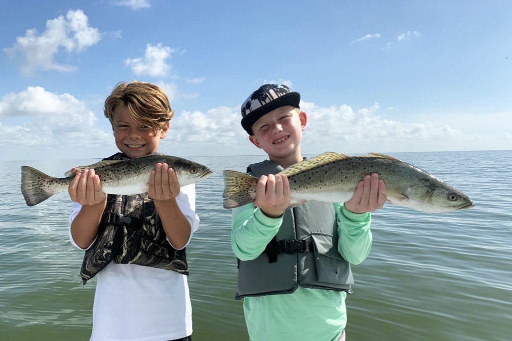Two boys pose with a Speckled Trout each on a boat on a sunny day with water behind them