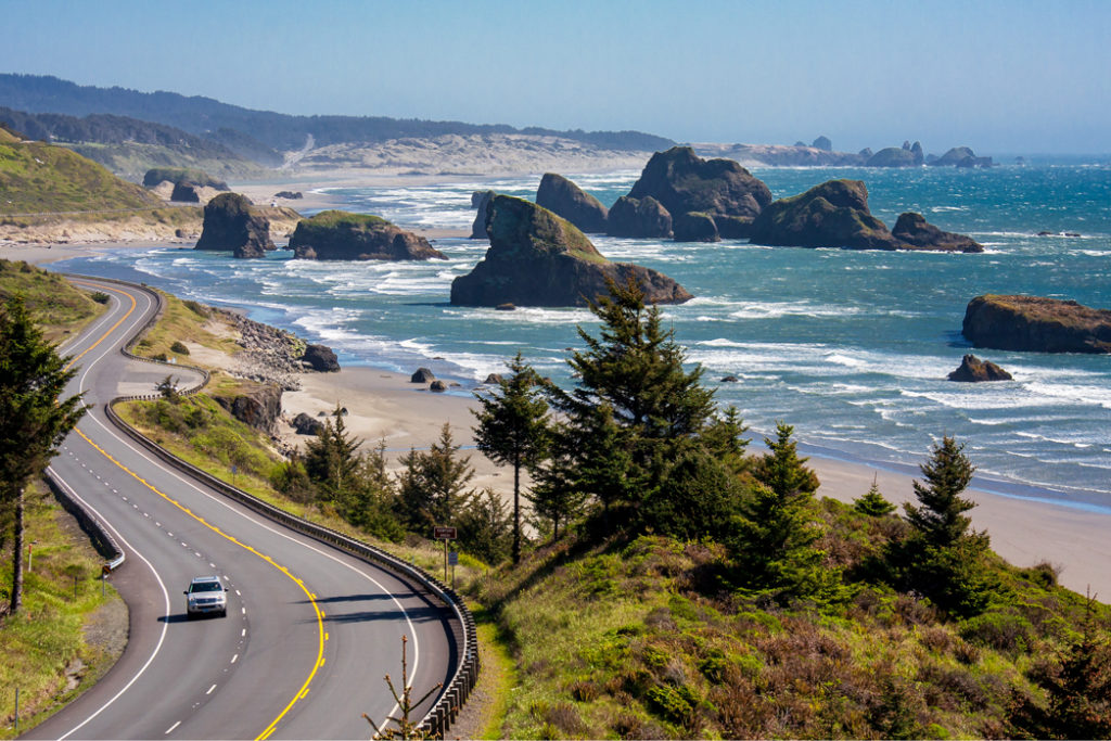 A view of Cannon Beach in Oregon with the highway running alongside the ocean with large rocky structure protruding out of it