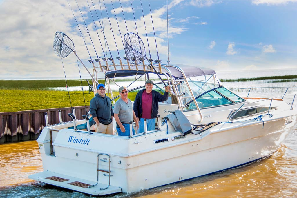 Three fishermen on a charter boat, with turbid waters and blue skies