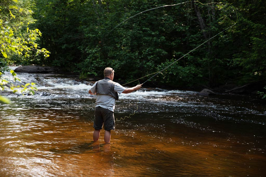 A fly fisherman casting a line in Michigan River