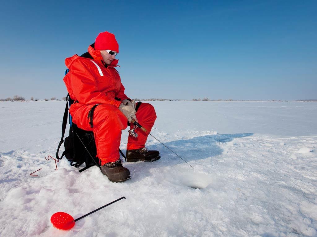 A man ice fishing on a frozen lake