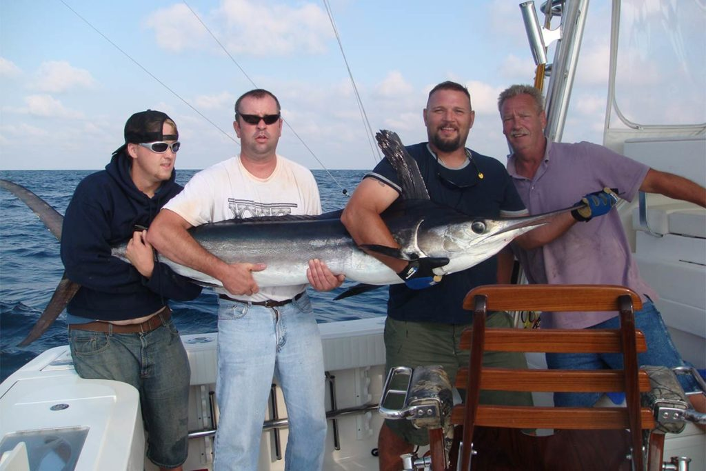 Four anglers hold a large Marlin caught in the deep waters offshore