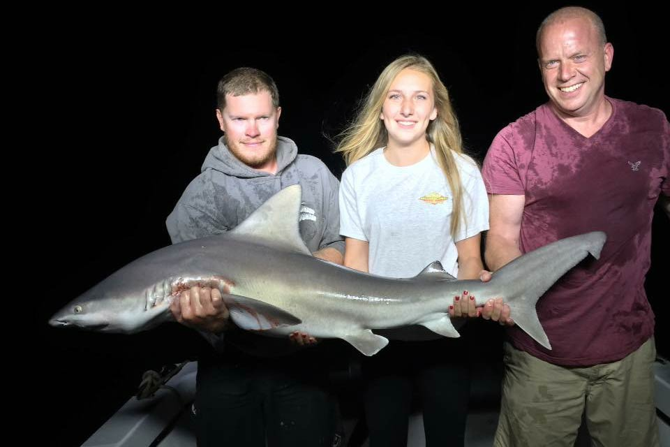 Three anglers hold a Shark caught while night fishing