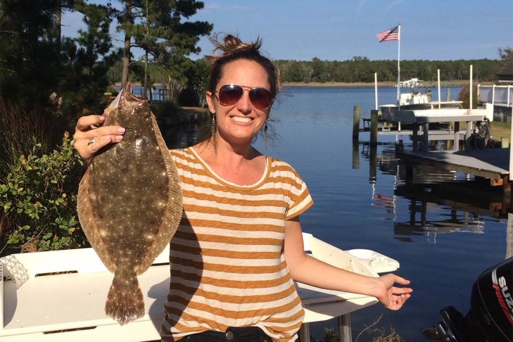 A woman holds a Fluke while back on shore after fishing out of Ocean City