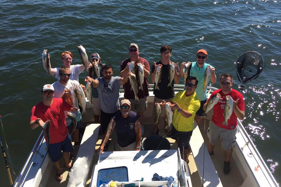 A group of smiling anglers hold their catches aboard an Ocean City head boat