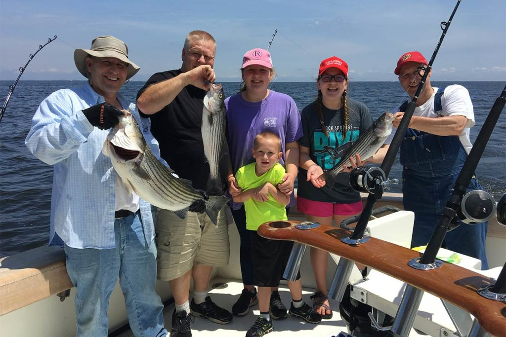 A family of anglers hold their Rockfish caught fishing at Ocean City