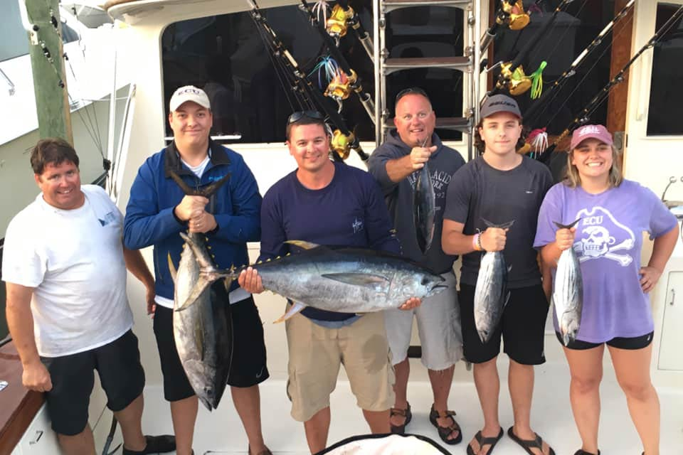 A group of anglers hold some Tuna caught while fishing offshore in the Atlantic