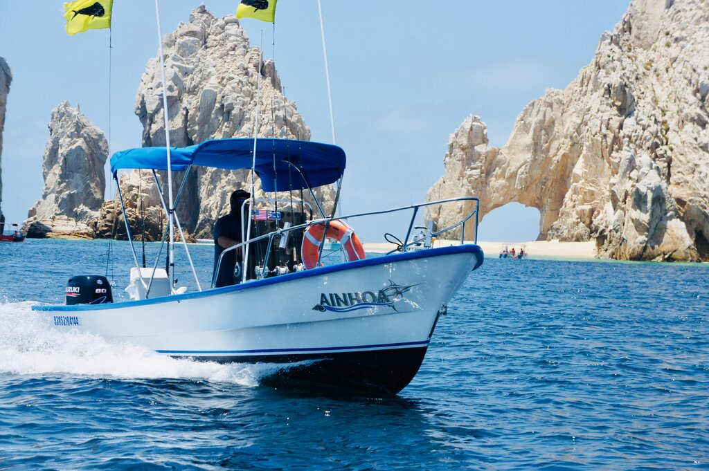 A charter fishing boat with the famous arch of Cabo San Lucas in the background