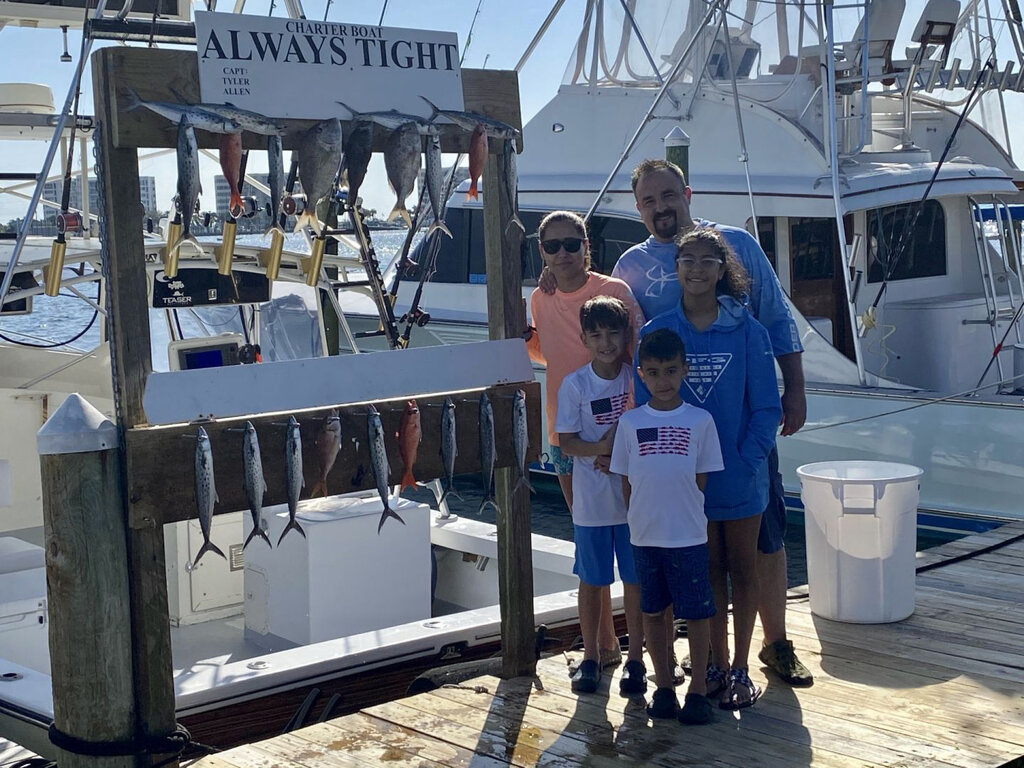 an angling family posing with their catch at the marina in Destin
