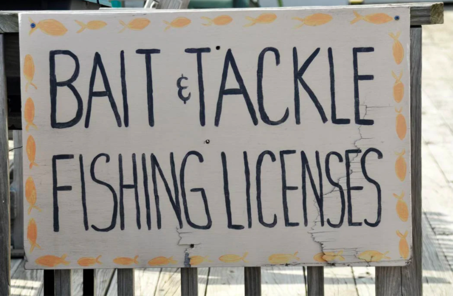 """A photo of a hand-painted shop sign reading """"Bait and Tackle Fishing License"""""""