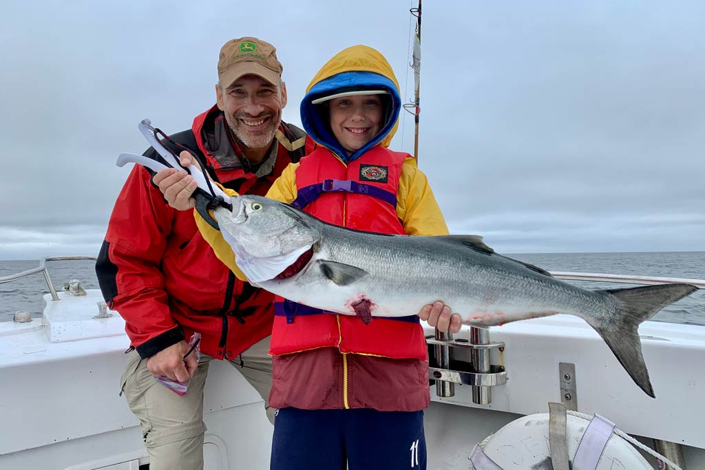 A man and a child standing on a boat, the child holding a big Bluefish, with cloudy skies in the background