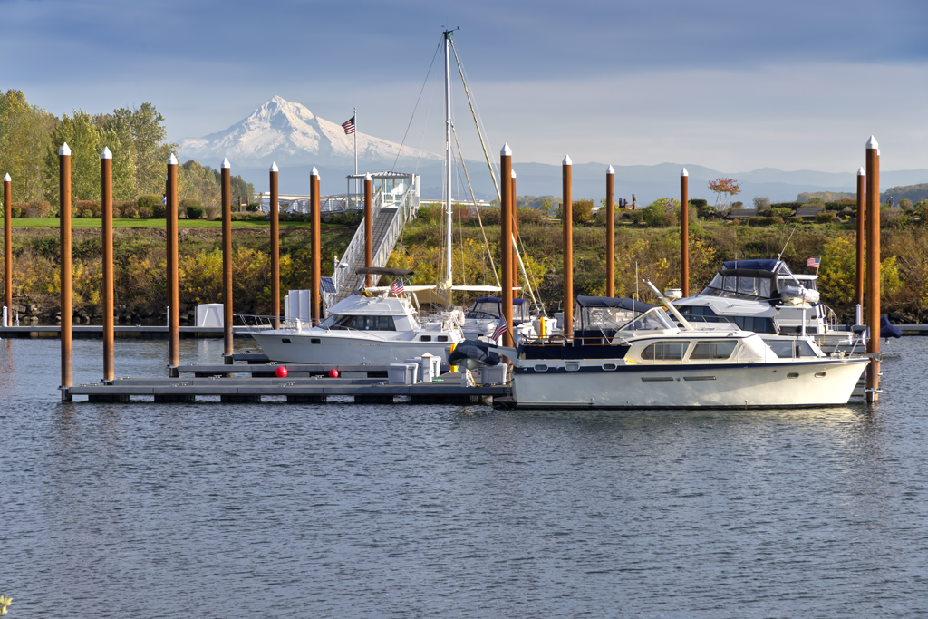 Charter boats docked in a marina along the Columbia River with mountains in the background