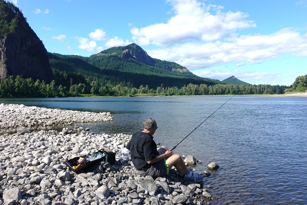 A man sits on the rocky banks of the Columbia River on a sunny day casting a line into the water