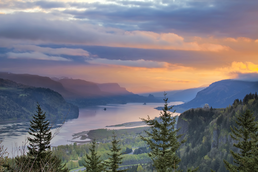 A view of the Columbia River at sunset with mountains and trees