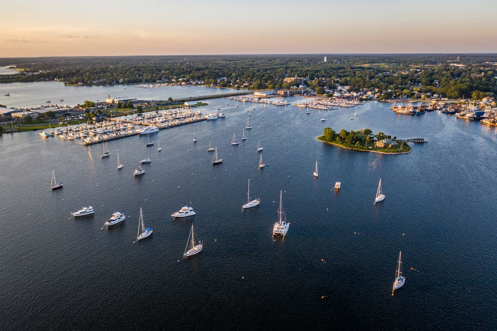 An aerial view of a bay in Massachusetts with sailboats dotted on the water