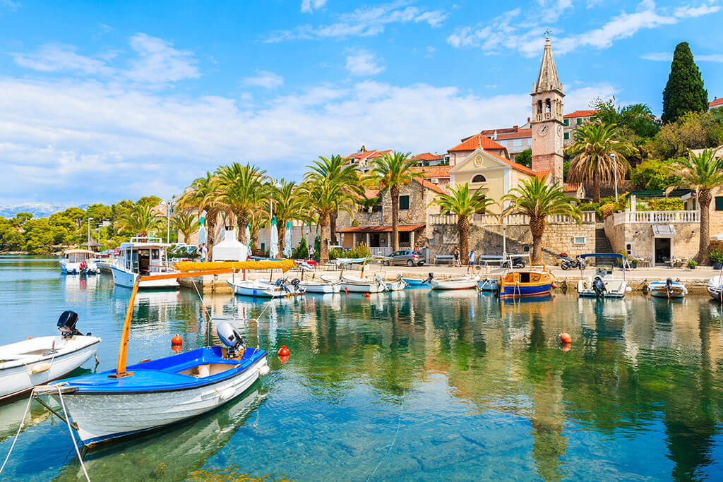 A traditional fishing boat near an old stone citadel in Croatia, Europe