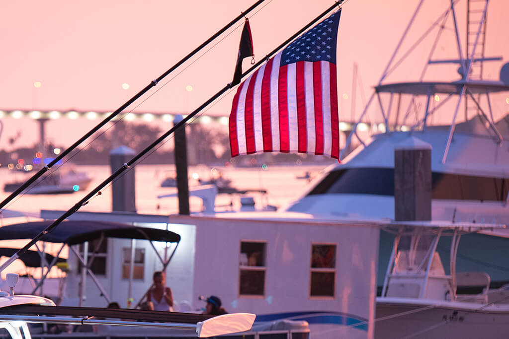 A US flag hanging near fishing boats in a harbor