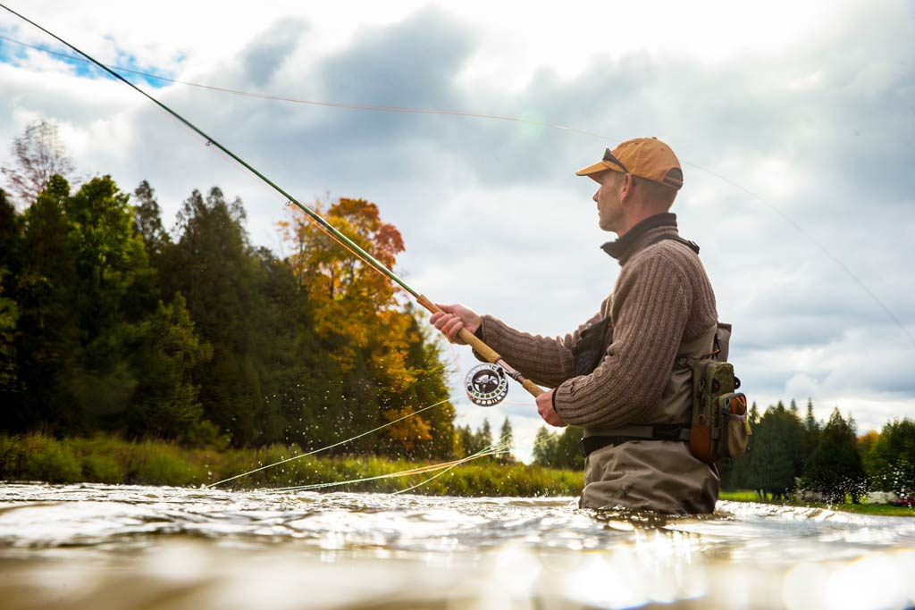 A fly fisherman wading in a river, with a fly rod in his hands, trees in the background