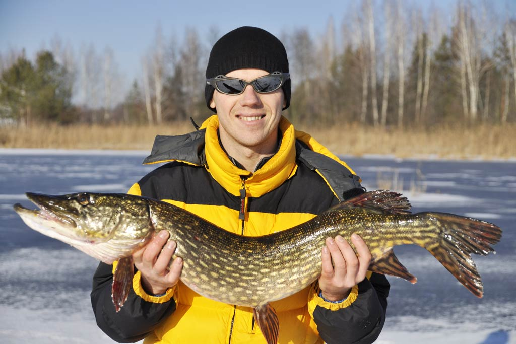 A smiling angler in winter clothes and sunglasses standing on ice, holding a Northern Pike