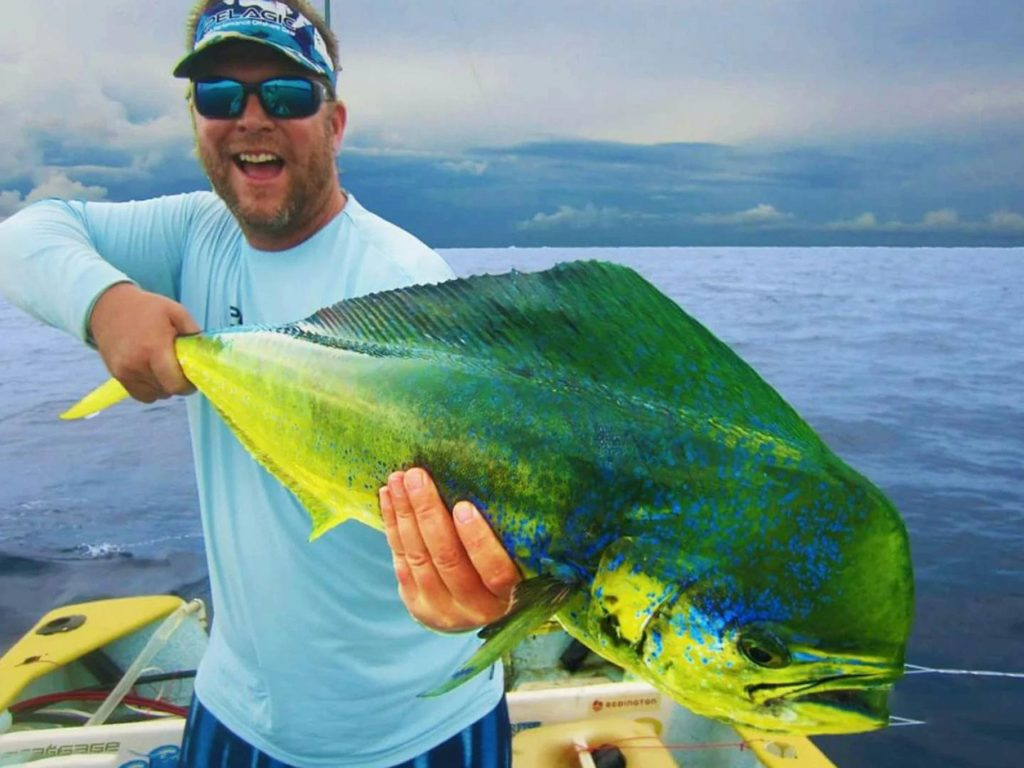 An angler holding a big Mahi Mahi on a boat