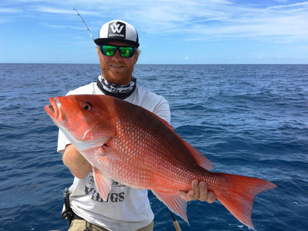 An angler holding a Red Snapper on a boat
