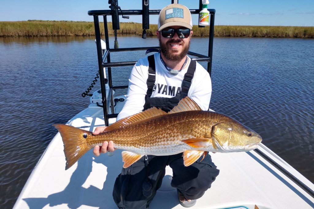 A smiling angler holding a Redfish aboard a skiff in the Mosquito Lagoon.