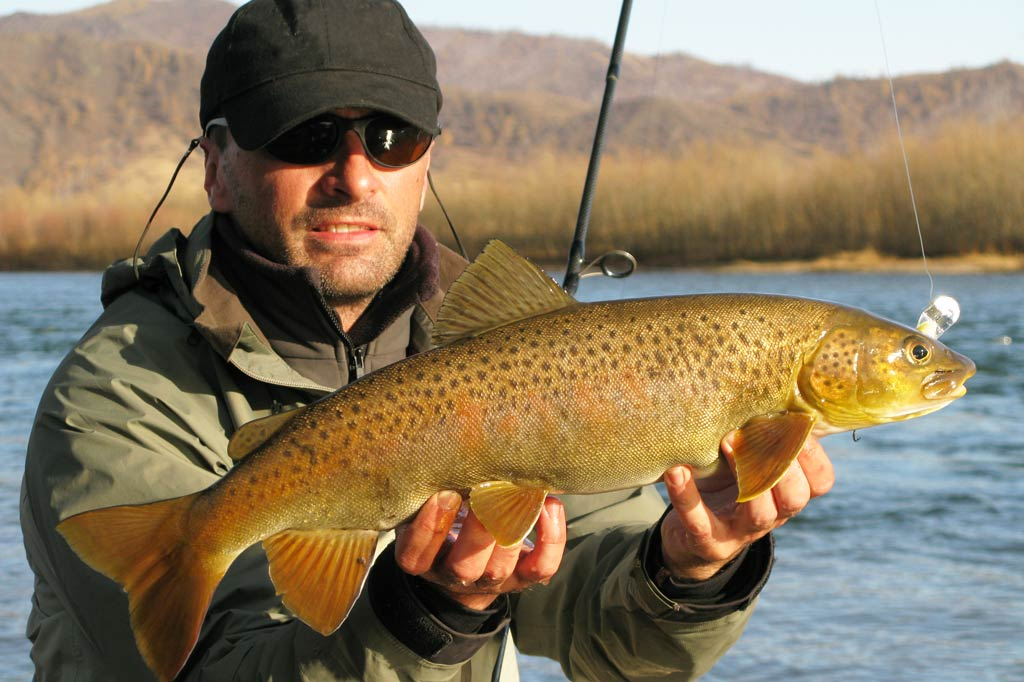 A man wearing sunglasses and a hat holding a Brown Trout with water and autumn woods in the background