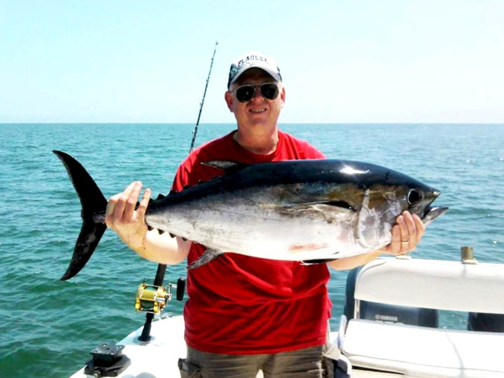 An angler holding a big Blackfin Tuna on a boat