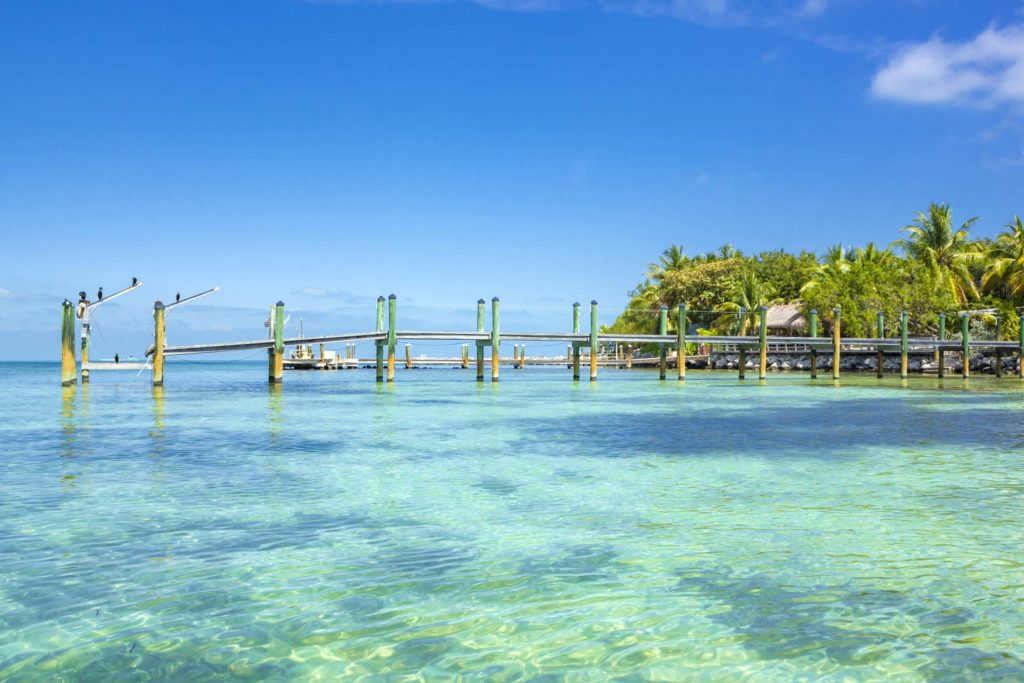 A typical Florida Keys landscape, with turquoise blue waters and a dock coming onto the water