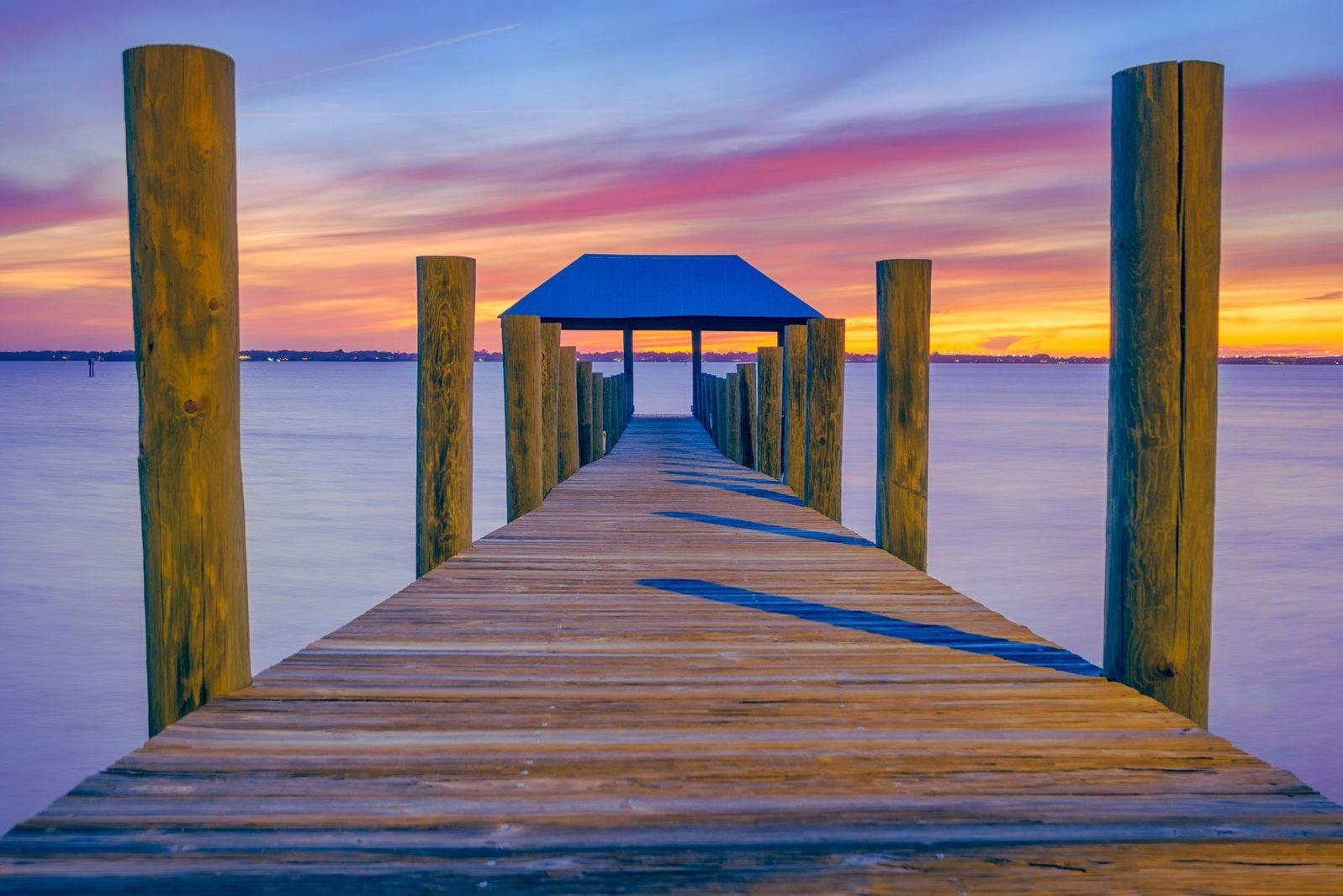 A sunset shot from a fishing pier on Hutchinson Island, one of the best summer fishing destinations in Martin County, Florida, with a refuge house at the end of the pier